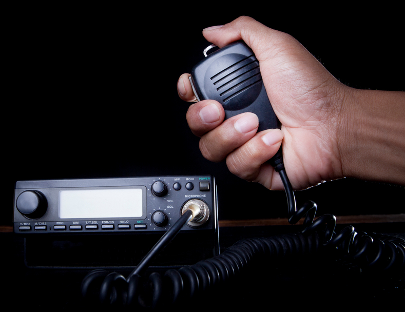 hand of Amateur radio holding speaker and press for radio communication theme ABL Circuits